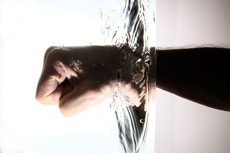 Close-Up Of Fist In Water Against White Background