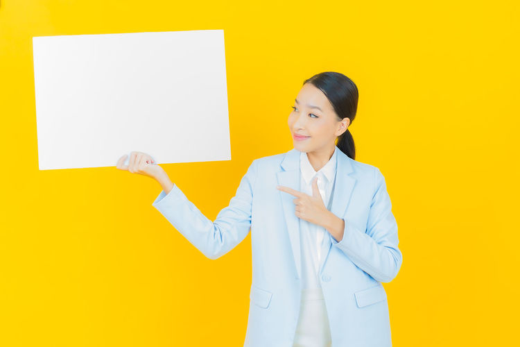 Mid adult woman standing against yellow wall