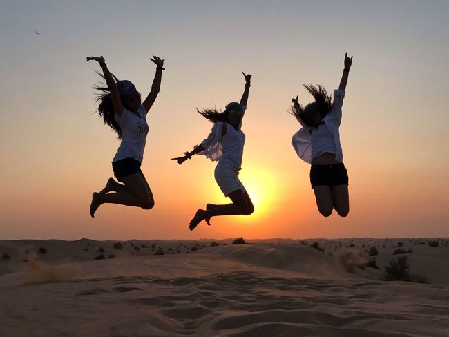 Connected By Travel Lost In The Landscape Mid-air Jumping Sunset Energetic Full Length Real People Fun Togetherness Leisure Activity Enjoyment Sand Sand Dune Desert Sky Outdoors Silhouette Lifestyles Girls Motion Nature Travel Dubai UAE