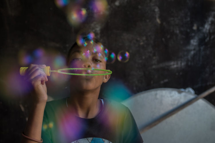 Colorful Blowing Bubble Bubble Wand Child Childhood Day Focus On Foreground Front View Headshot Holding Leisure Activity Lifestyles Males  One Person Portrait Real People