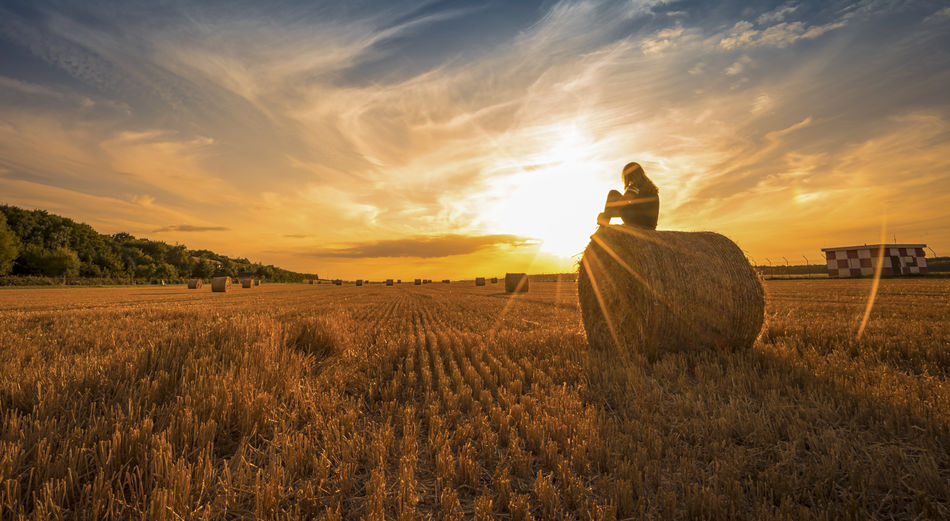 Woman Sitting On Hay Bale Against Sky During Sunset