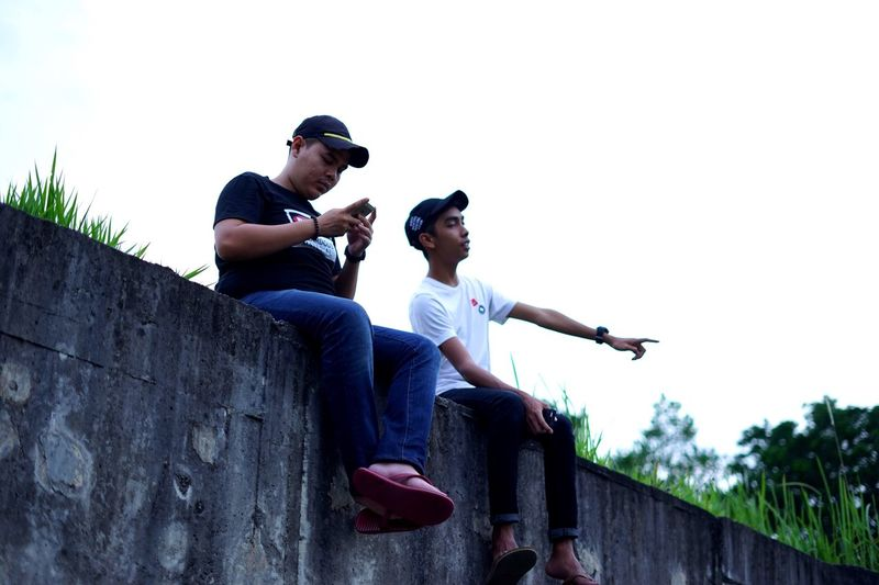 Two People Sitting Sunglasses Cap Full Length Low Angle View Casual Clothing Bonding Young Adult Men Baseball Cap Togetherness Outdoors Smiling Friendship Day Happiness People Only Men Horizontal Uitmdihatiku City Life Lifestyles Urban Cloud - Sky