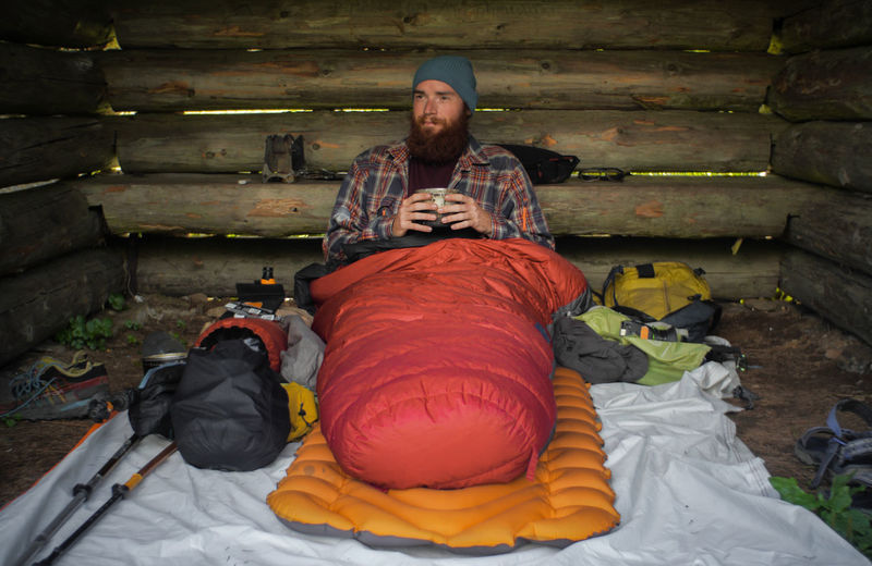 portrait of a caucasian male hiker laying on the ground in his sleeping bag Camping Freedom Hiking Man Morning Nature Travel Trekking Youth Adventure Beard Bivouac Caucasian Dirtbag Forest Homeless Lumberjack Male Outdoors Outside Portrait Sleeping Bag Sleeping Pad Young Adult