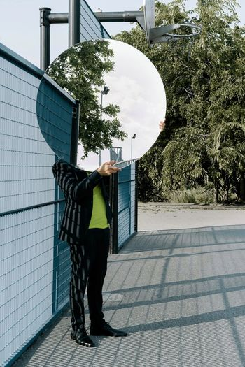 Man holding mirror while standing on footpath against trees