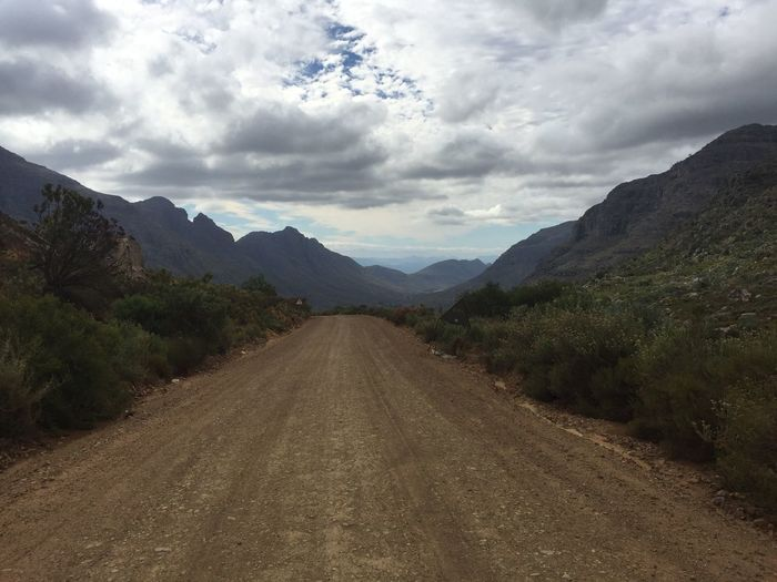 Dirt road against cloudy sky