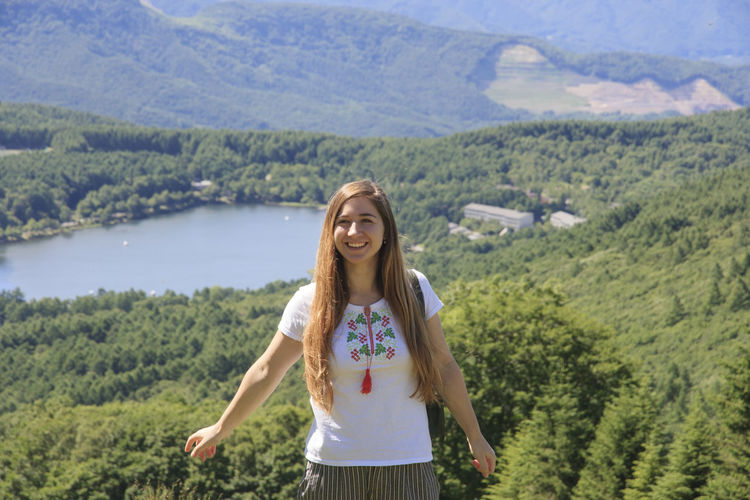 Smiling young woman standing against landscape