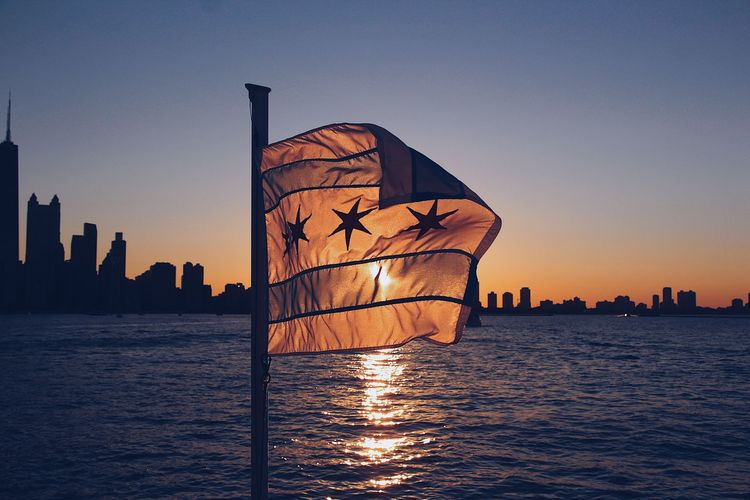 The flag Chicago Illinois Architecture Beauty In Nature Built Structure City Cityscape Clear Sky Illuminated Nautical Vessel No People Orange Color Outdoors Sailboat Scenics - Nature Sea Silhouette Sky Skyscraper Sunset Urban Skyline Water Waterfront
