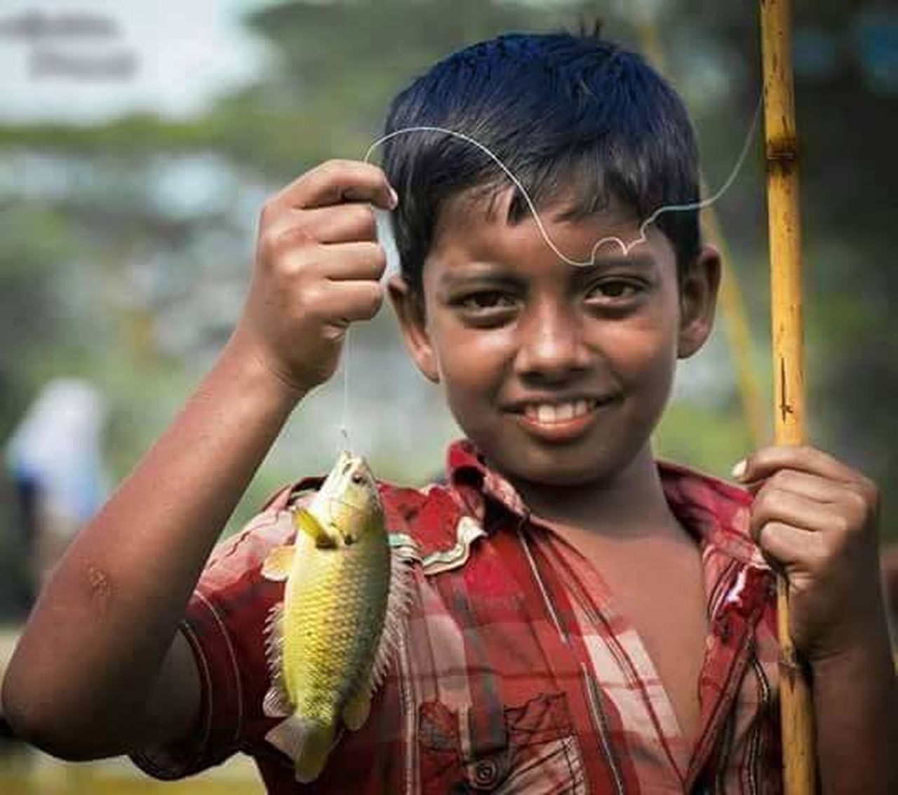 child, holding, childhood, one animal, children only, front view, one person, one girl only, happiness, fish, people, outdoors, girls, portrait, smiling, animal themes, looking at camera, day, trapped, reptile, close-up, freshness, adult