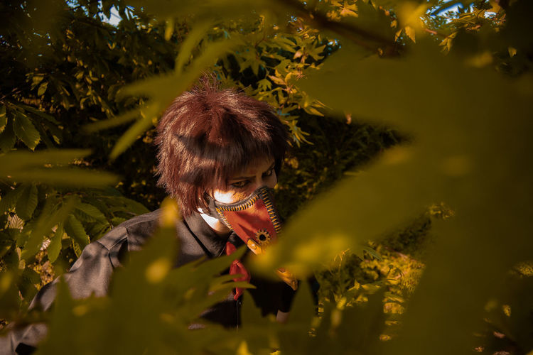 Portrait of woman with leaves in park