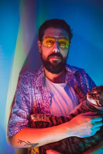 Cat Front View One Person Young Adult Beard Young Men Facial Hair Real People Leisure Activity Casual Clothing Lifestyles Portrait Waist Up Glasses Looking At Camera Mid Adult Blue Sitting Mustache Indoors  Friend Wearing Personal Perspective Barber Lumbersexual Blue Background One Mid Adult Man Only Colored Background Pink Background Purple Background