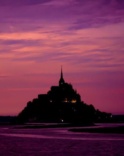 Le Mont Saint-Michel. Sunset Architecture Sky Built Structure Building Exterior Travel Destinations Water Waterfront Religion Silhouette No People Outdoors Cloud - Sky Place Of Worship Spirituality Nature Scenics Beauty In Nature Day Mont Saint-Michel Pink Background Perspectives On Nature