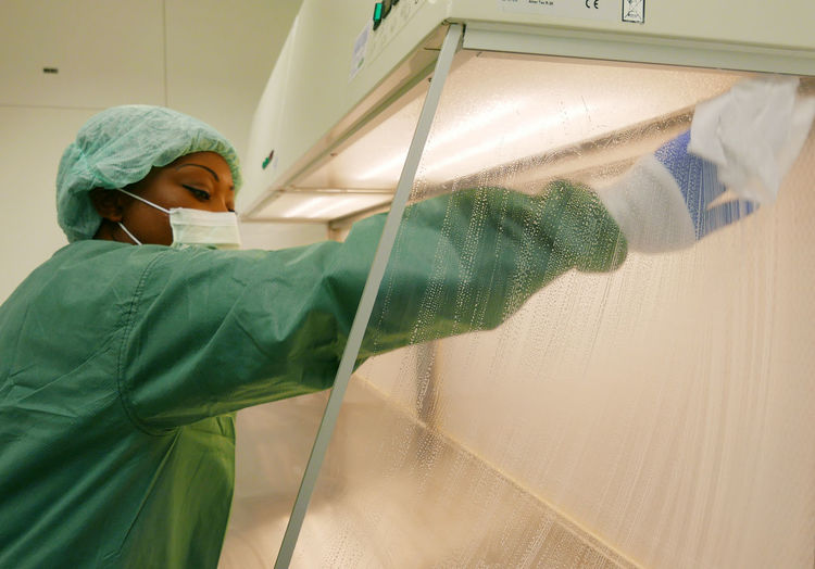 Side view of nurse cleaning glass at hospital