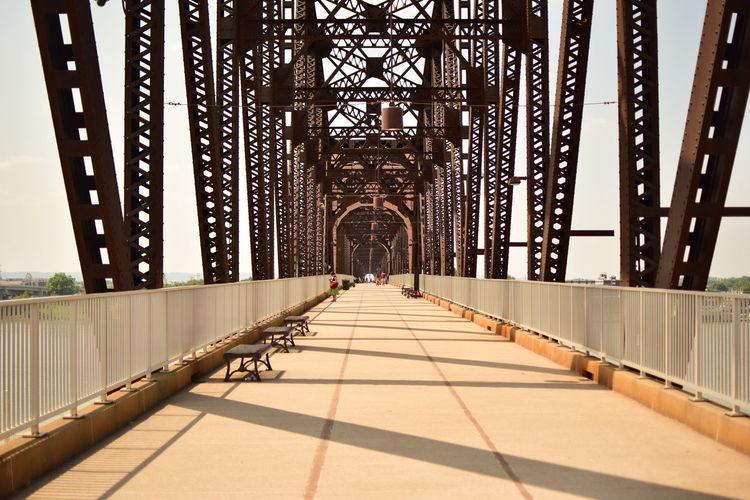 Footbridge in city against sky