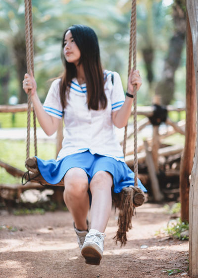 One Person Swing Real People Full Length Hairstyle Long Hair Sitting Casual Clothing Lifestyles Playground Focus On Foreground Leisure Activity Day Women Rope Hair Front View Child Girls Outdoors Rope Swing Outdoor Play Equipment Teenager