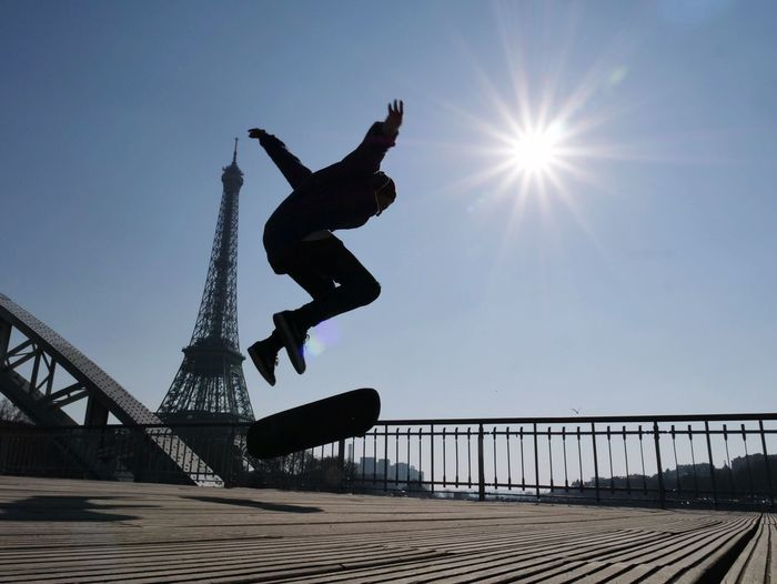 Low angle view of silhouette man skateboarding against eiffel tower