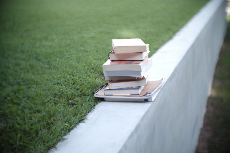 Books stacked on retaining wall