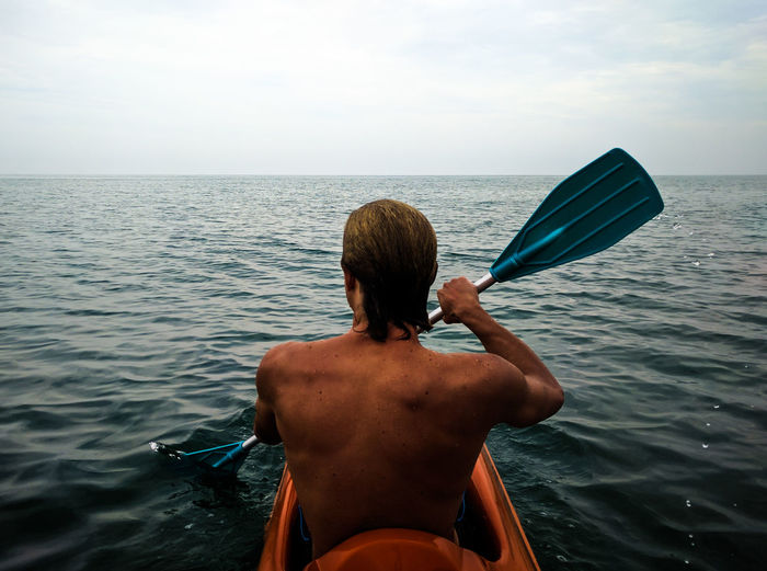 Rear View Of Shirtless Man Kayaking In Sea Against Sky