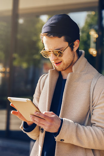 Young man using digital tablet outdoors