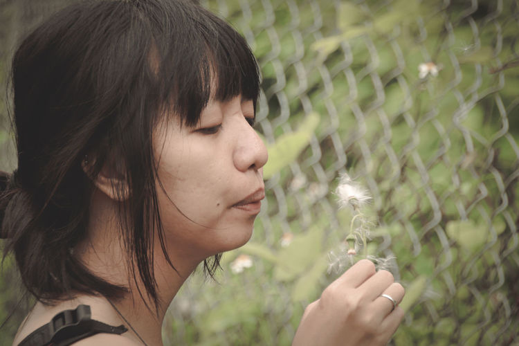 Close-up of woman blowing dandelion seed