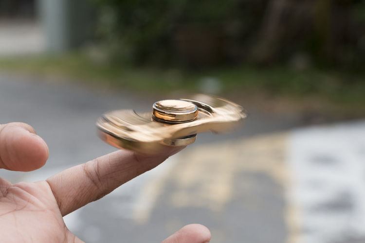 Cropped hand spinning fidget spinner on road