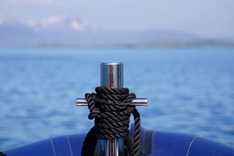 Close-up of black rope tied on boat in river