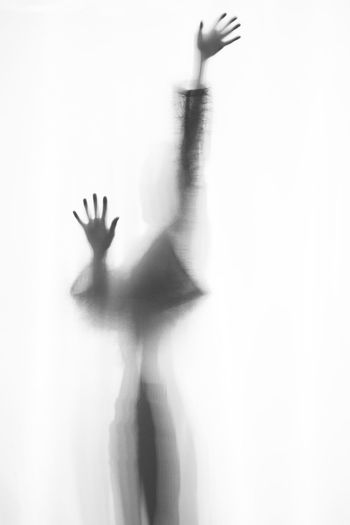 Human Hand Hand Silhouette One Person Unrecognizable Person Shadow Indoors  Human Body Part Fear Frosted Glass Spooky Mystery Horror Real People Waist Up Dancing Glass - Material Human Arm Lifestyles Arms Raised Aggression  Human Limb Woman