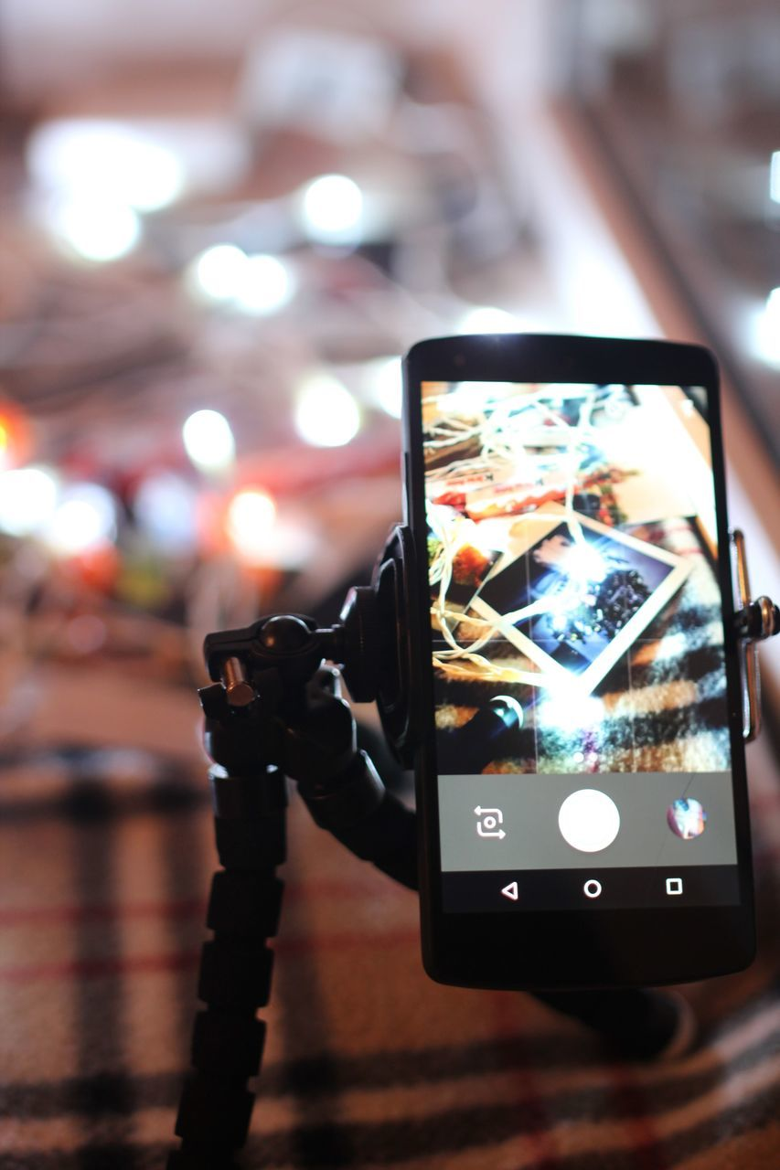 photography themes, illuminated, wireless technology, focus on foreground, technology, photographing, camera - photographic equipment, portable information device, close-up, mobile phone, night, no people, indoors