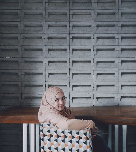 Portrait of young woman sitting on chair against wall