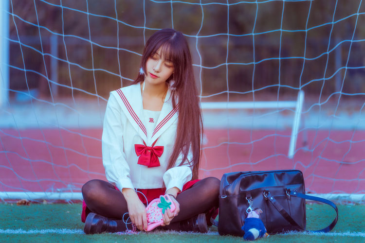 Young woman listening to music while sitting against net on soccer field