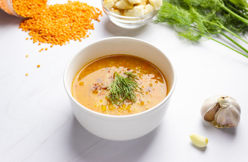 Red lentil soup with ingredients on a light background. traditional turkish or arabic spicy lentil