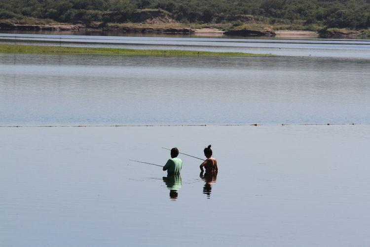 Man And Woman Fishing In Lake