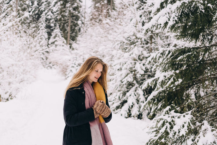Woman standing on snow covered trees during winter