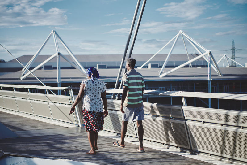 Rear view of woman on bridge against sky