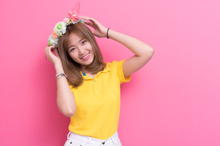 Portrait of beautiful woman wearing flowers against pink background