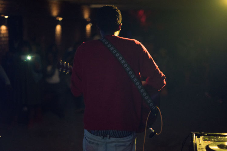 Rear View Of Man Playing Guitar On Stage At Night