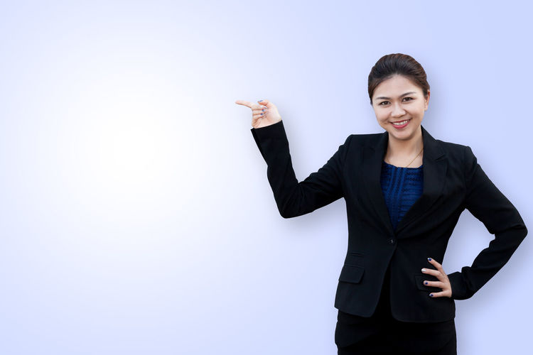 Asian business woman point up Colored Copy Space Isolated Smart Woman Advertisement Background Business Business Person Businesswoman Confidence  Copy Space Corporate Business Empty Finger Gesturing Looking At Camera One Person Pointing Portrait Smiling Studio Shot Suit Waist Up Well-dressed