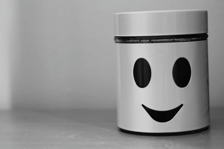 Close-up of smiley anthropomorphic face on mug against wall