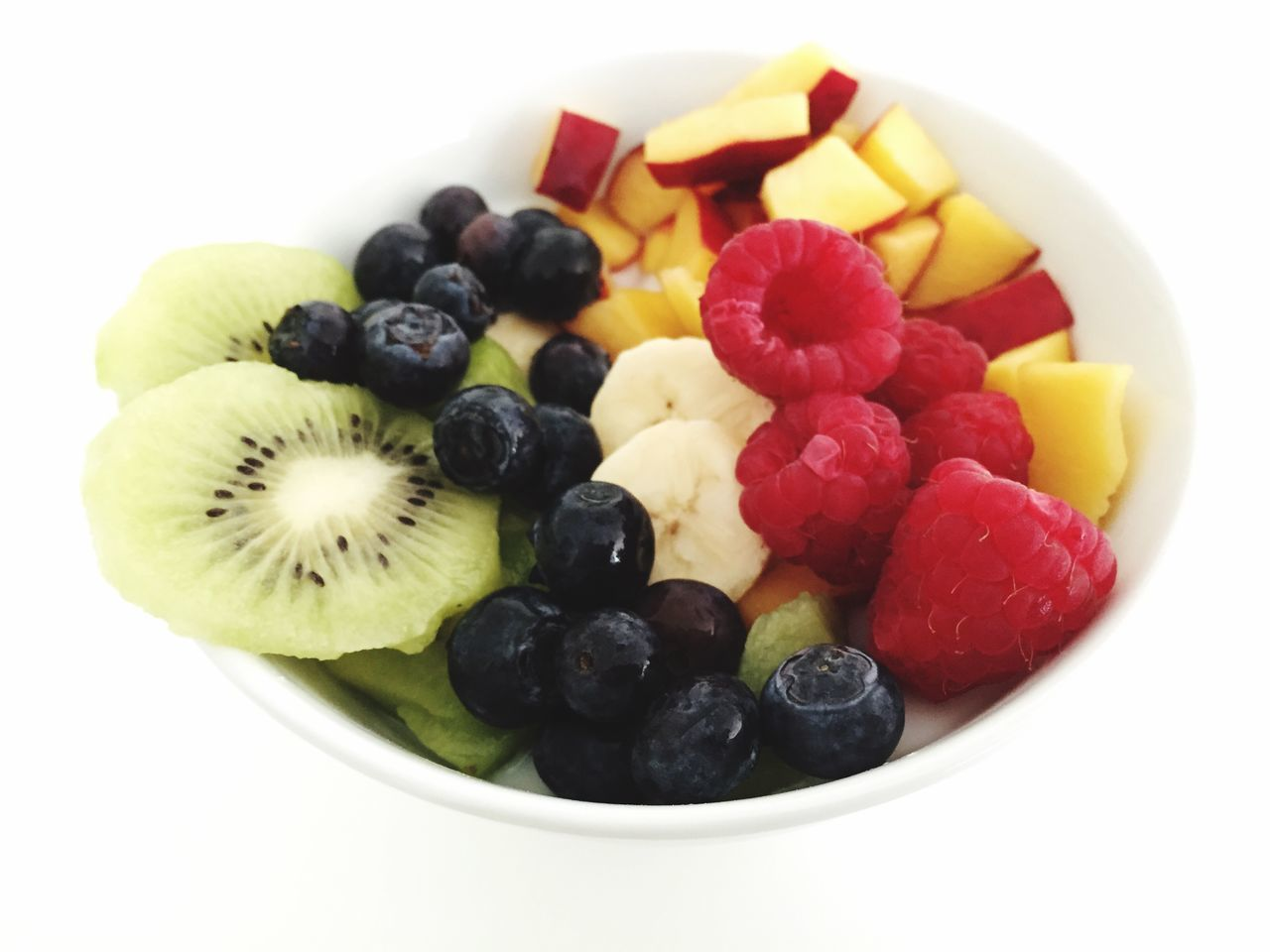 Close-Up Of Fruits In Bowl Over White Background