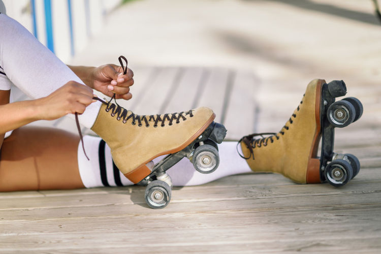 Low Section Of Man Tying Lace Of Roller Skates