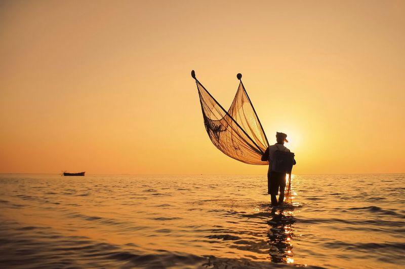 Man With Net In Sea Against Clear Sky During Sunset