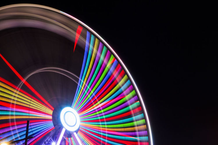 Low angle view of illuminated ferris wheel spinning at night