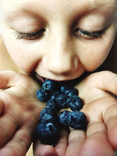 Close-up of girl eating blueberries