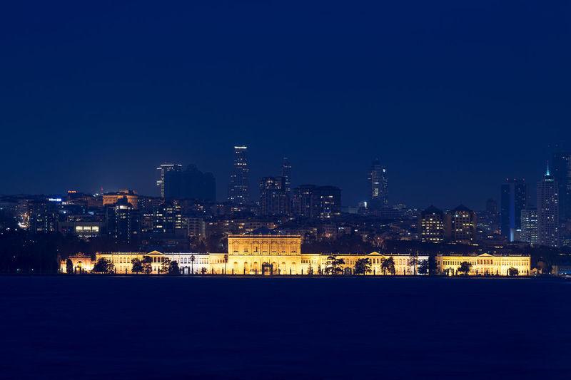 Illuminated dolmabahce palace by bosphorus at night