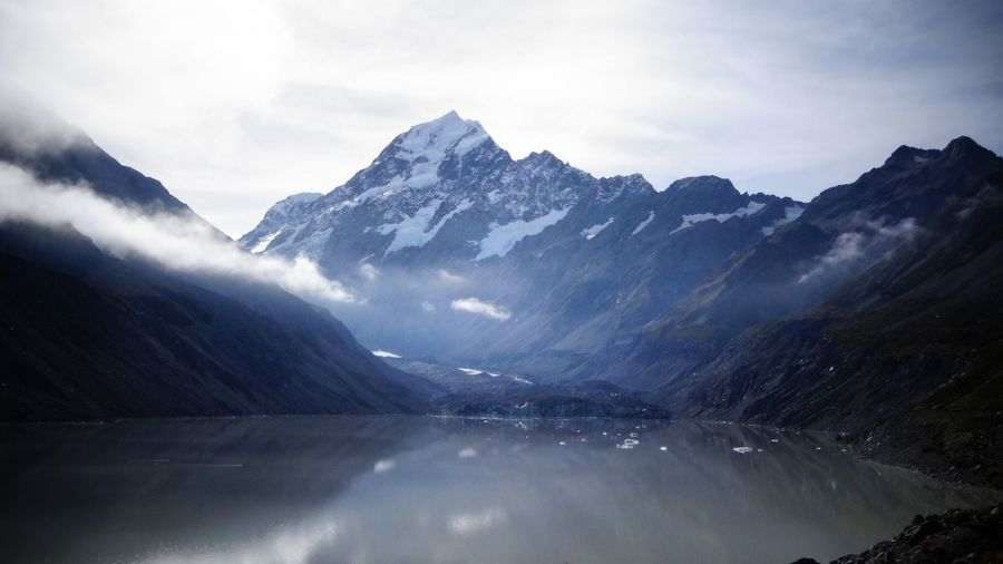 Scenic view of aoraki mt cooks by river against cloudy sky