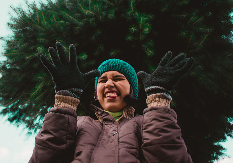 Low angle view of woman making face while gesturing against tree