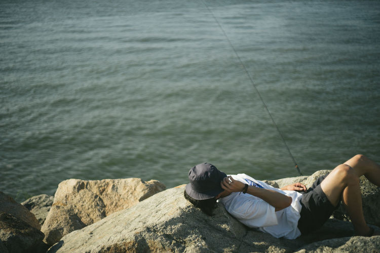 High Angle View Of Man Relaxing With Hat On Rocks By Sea