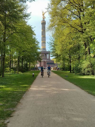 Male friends cycling on walkway in park against berlin victory column
