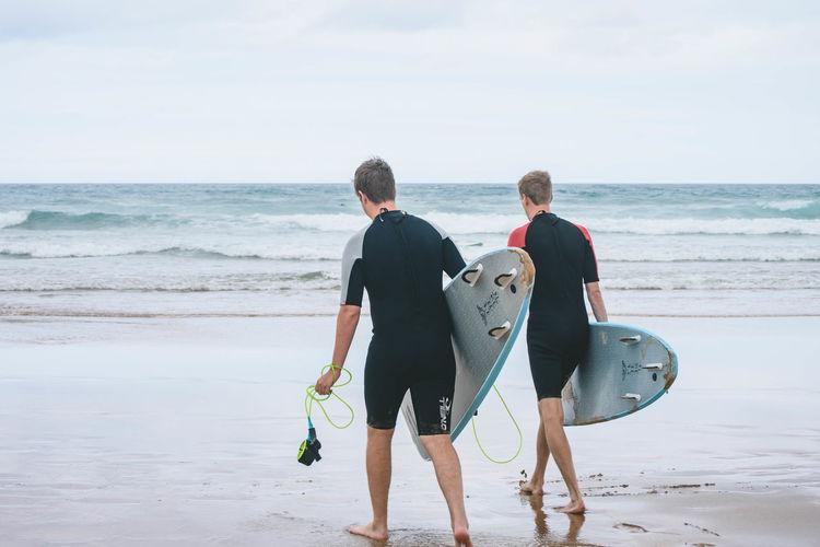 Full length of men on beach against sky