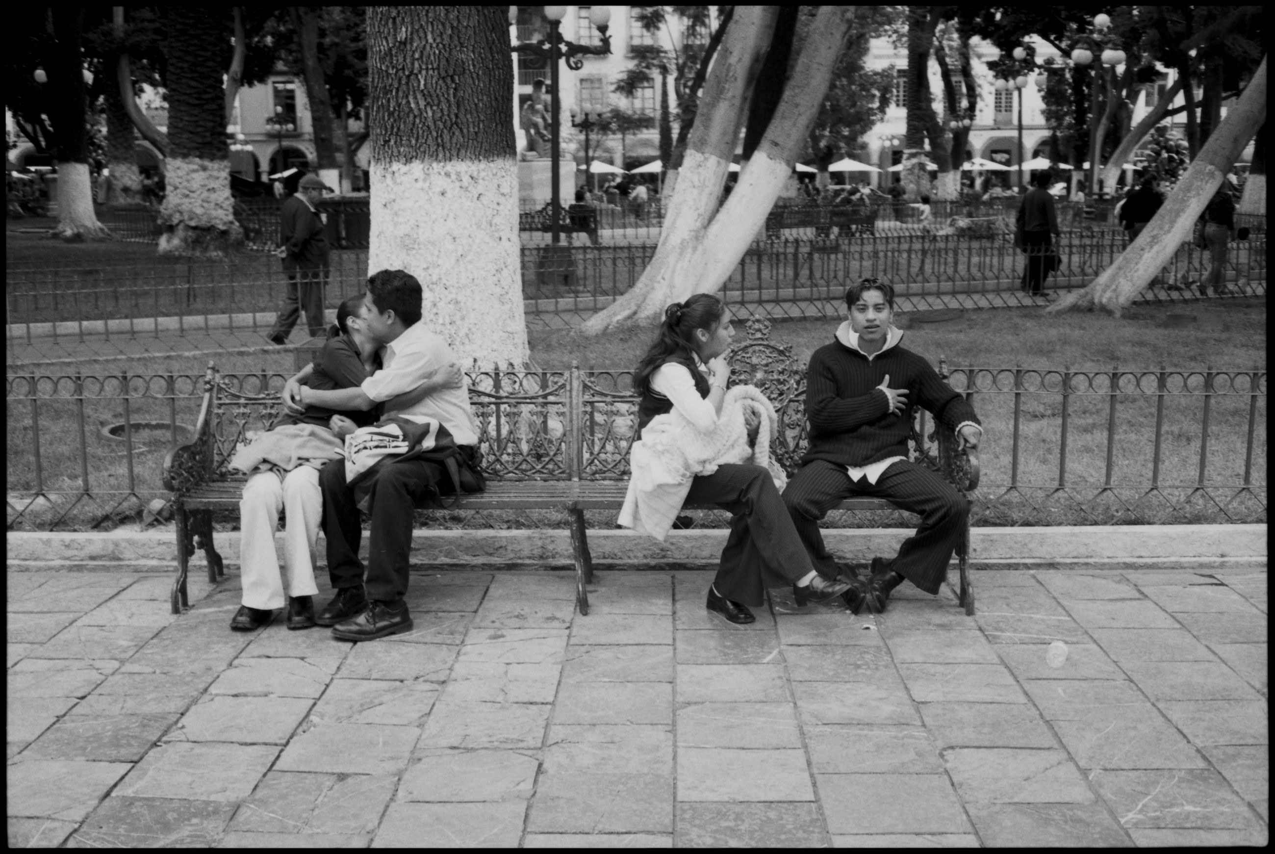 sitting, group of people, seat, men, full length, bench, real people, people, women, adult, architecture, casual clothing, lifestyles, relaxation, city, day, young men, leisure activity, building exterior, street, paving stone