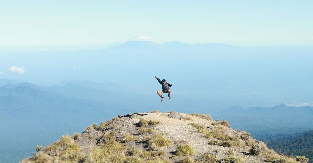 Happy mature man jumping on mountain against sky